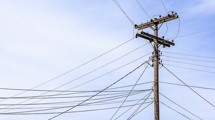 Photo of utility pole with many different lines attached