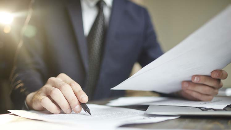 Photo of man in business suit reviewing documents