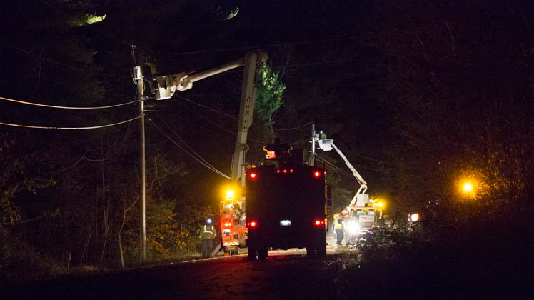 Photo of lineworkers repairing power lines at night.