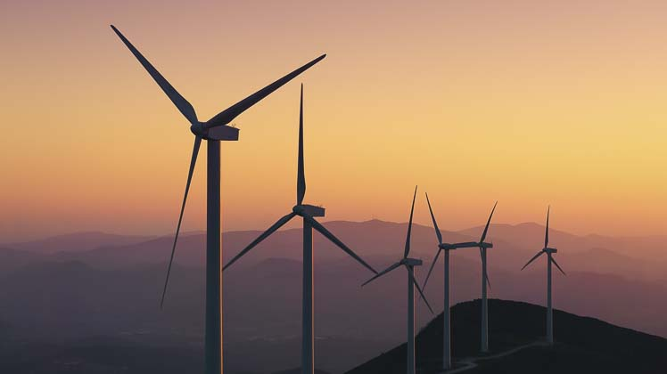 Six wind turbines at sunset