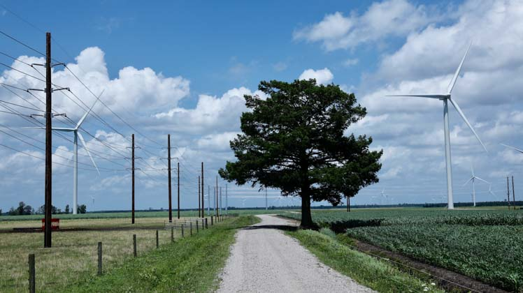Photo of wind turbines and transmission lines in a rural area